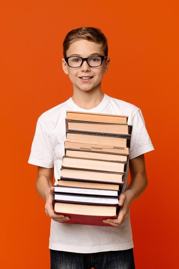 Garçon diligent mignon d'étudiant en verres avec le tas des livres images stock
