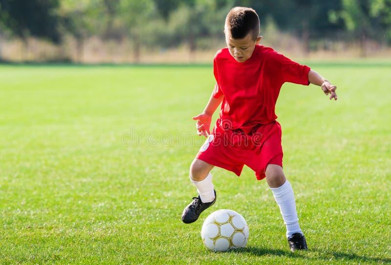Garçon donnant un coup de pied la bille de football images stock