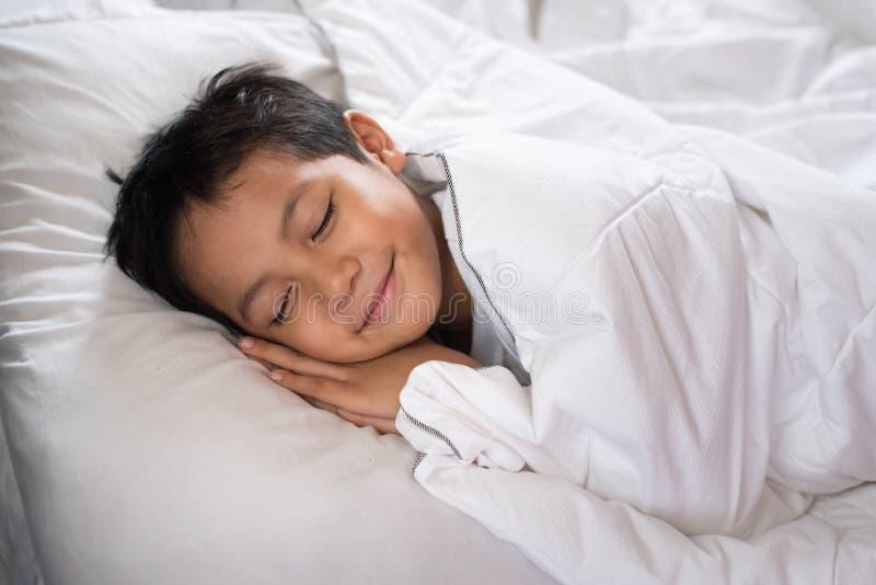 Garçon dormant avec le visage de sourire sur le drap et l'oreiller blancs photographie stock libre de droits