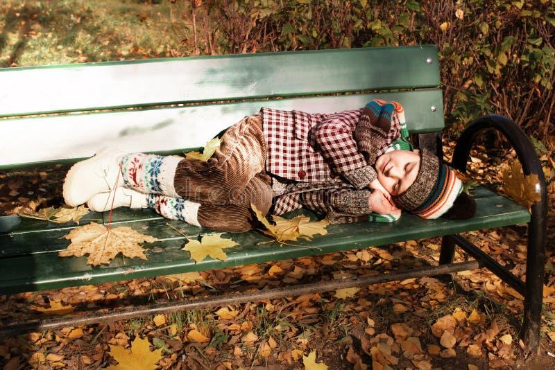 Garçon dormant sur le banc de stationnement en automne images libres de droits