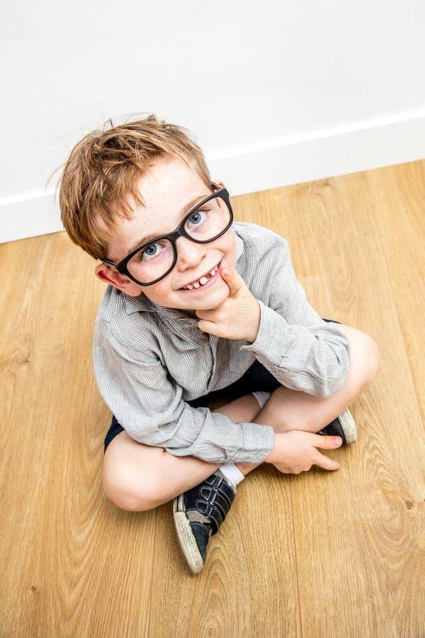 Garçon doué de sourire avec les lunettes intelligentes et les disparus de dent assis image libre de droits