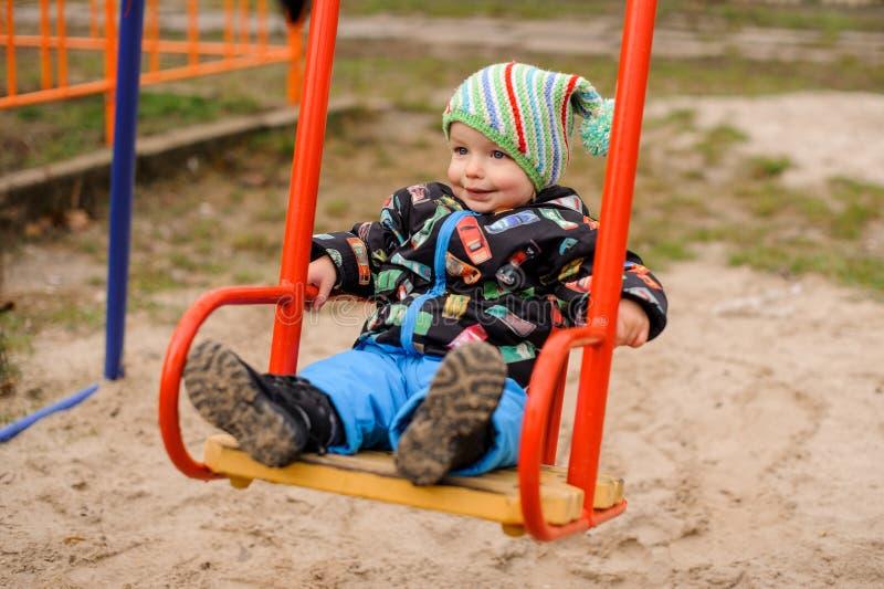 Garçon doux d'enfant en bas âge souriant sur une oscillation images stock