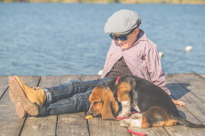 Garçon doux jouant avec son chien par la rivière images stock
