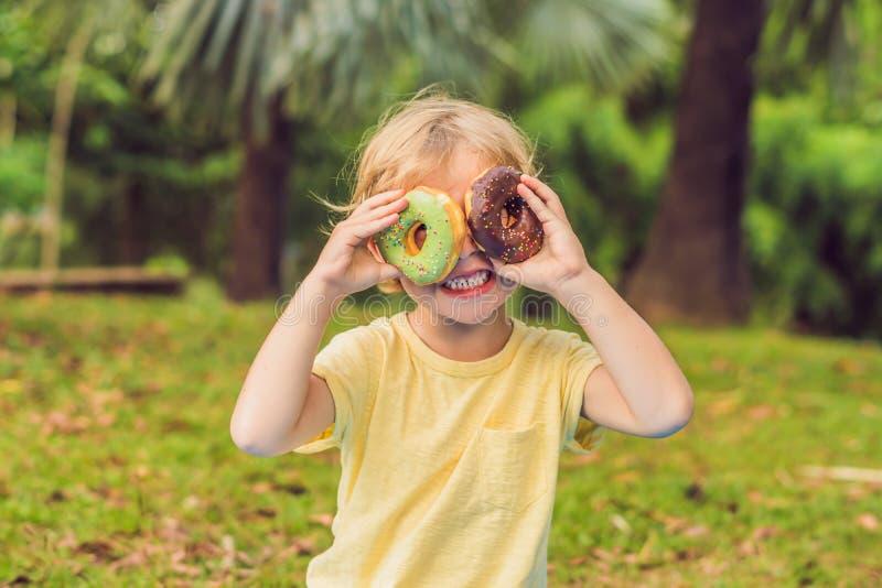 Garçon drôle avec le beignet l'enfant a l'amusement avec le beignet Nourriture savoureuse pour des enfants Temps heureux extérieu photographie stock