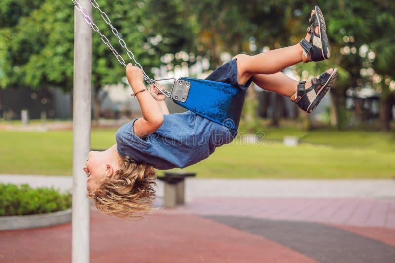 Garçon drôle d'enfant ayant l'amusement avec l'oscillation à chaînes sur le terrain de jeu extérieur enfant balançant le jour cha image libre de droits