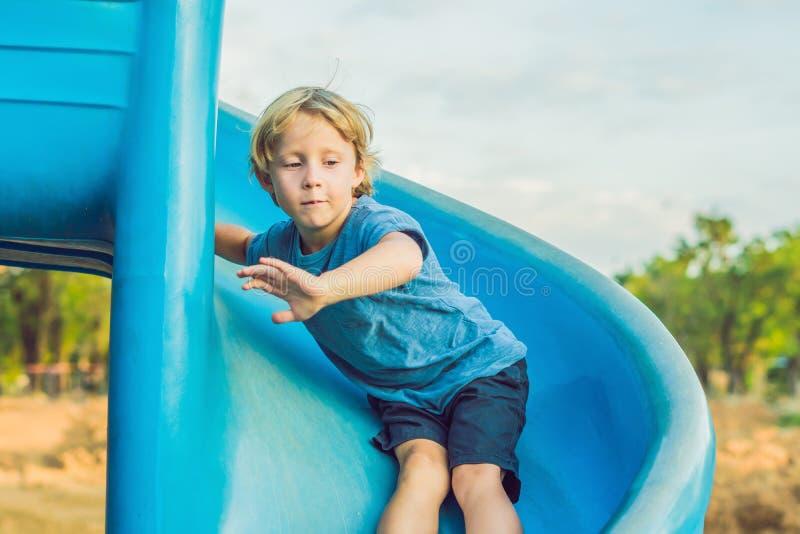 Garçon drôle d'enfant en bas âge ayant l'amusement sur la glissière sur le terrain de jeu photo libre de droits