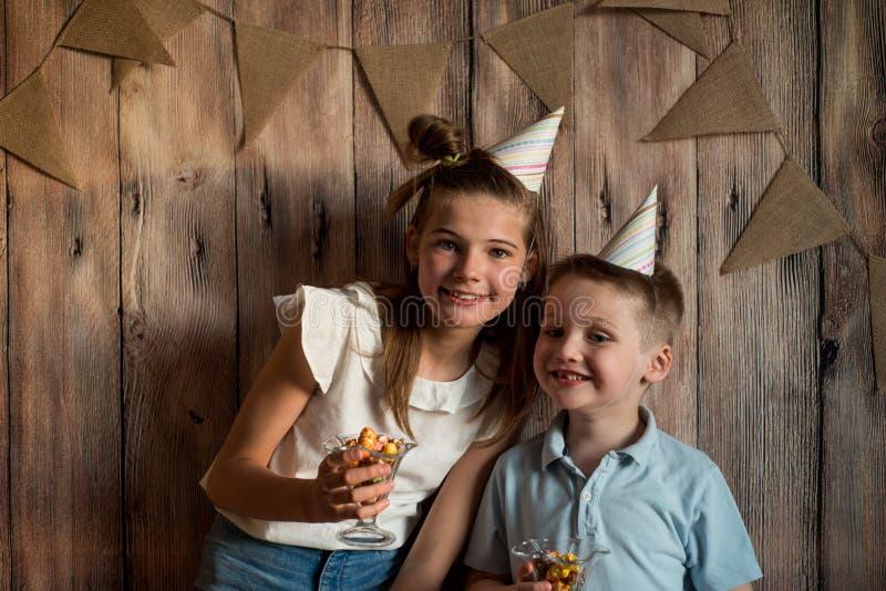 Garçon drôle et fille mangeant du maïs éclaté, riant d'une partie fond en bois avec des drapeaux, fête d'anniversaire gaie image stock