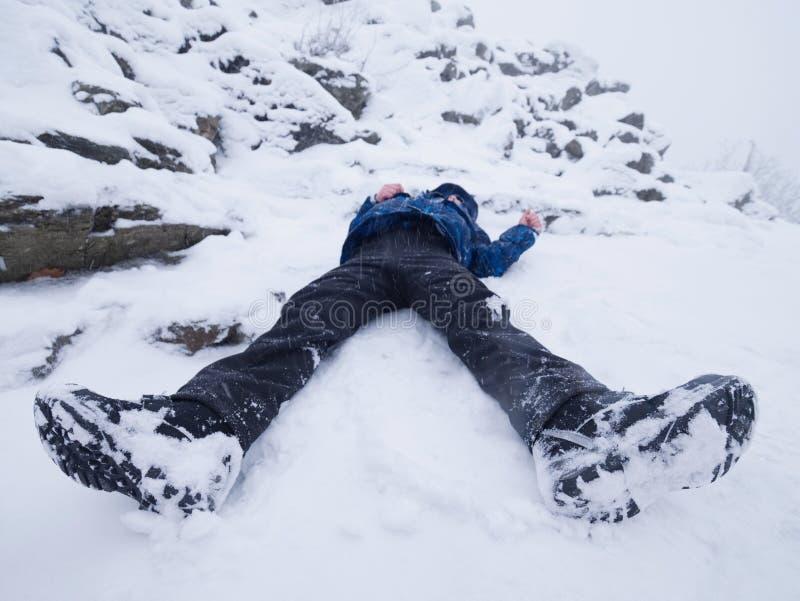 Garçon drôle s'étendant en congère Badinez le jeu de jeu dans la neige fraîche sur la colline pierreuse photo stock