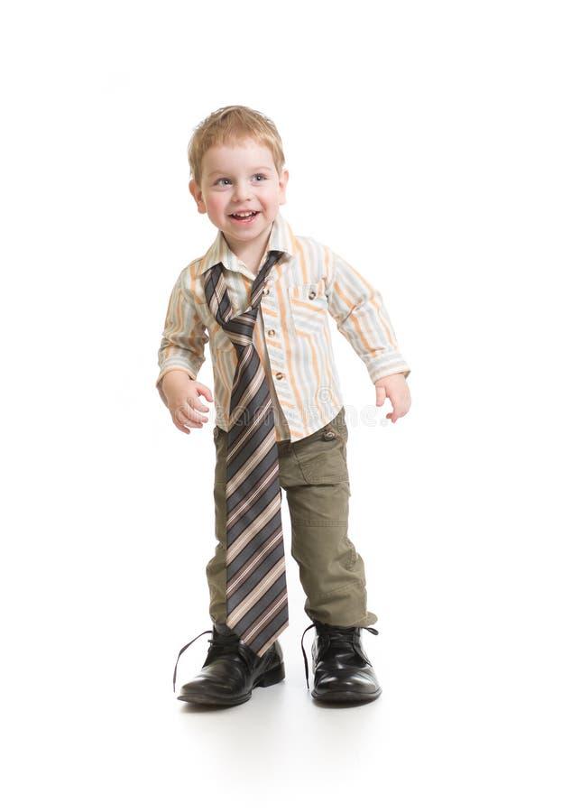Garçon drôle jouant dans des chaussures du grand père d'isolement images stock