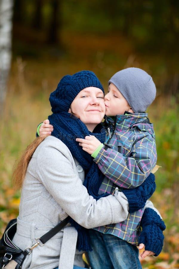 Garçon embrassant le sien mère extérieure images libres de droits