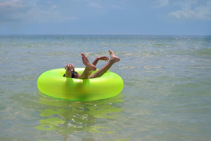 Garçon en anneau gonflable de plage image stock
