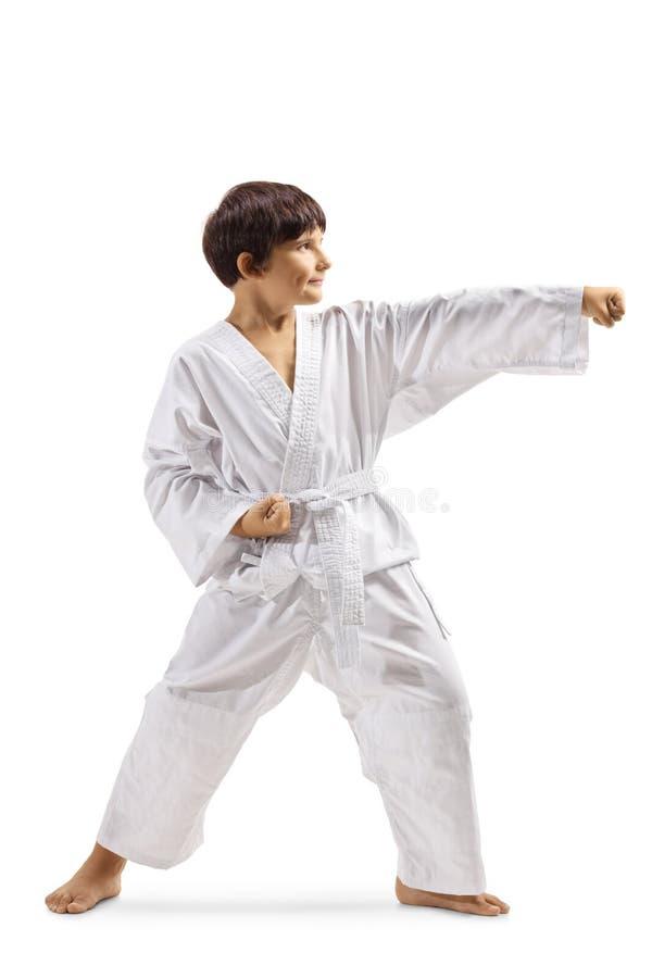 Garçon en arts martiaux de pratique d'un kimono blanc photo stock