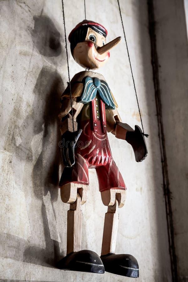 Garçon en bois de marionnette de ficelle accrochant sur un mur image stock