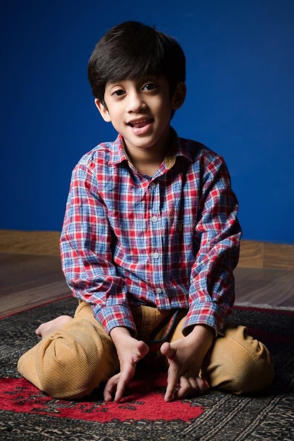 Garçon en bonne santé heureux s'asseyant sur une couverture ombres images libres de droits