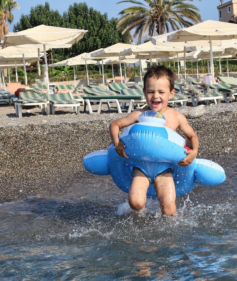 Garçon en cercle de natation, courses dans la mer photographie stock libre de droits