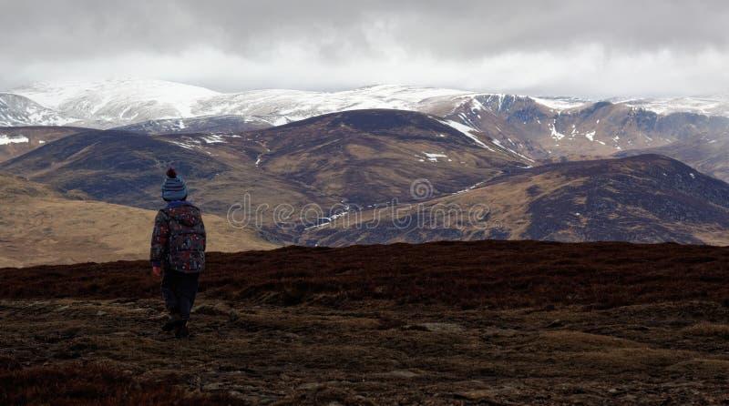 Garçon en montagnes de Cairngorm en Ecosse photo libre de droits