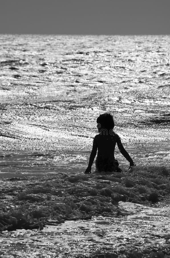 Garçon en vague déferlante approximative à la plage en noir et blanc photo libre de droits