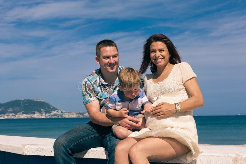 Garçon enceinte heureux de couples et d'enfant sur la côte images libres de droits