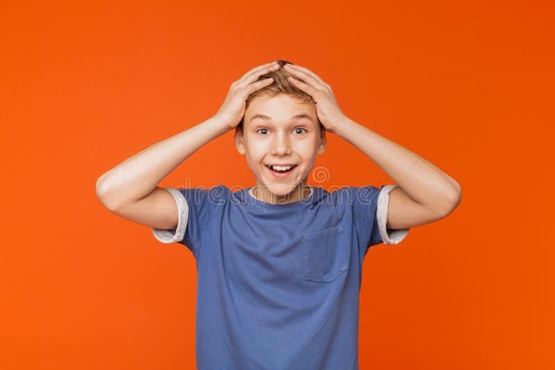 Garçon enthousiaste Surprised petit tenant des mains sur la tête photos stock