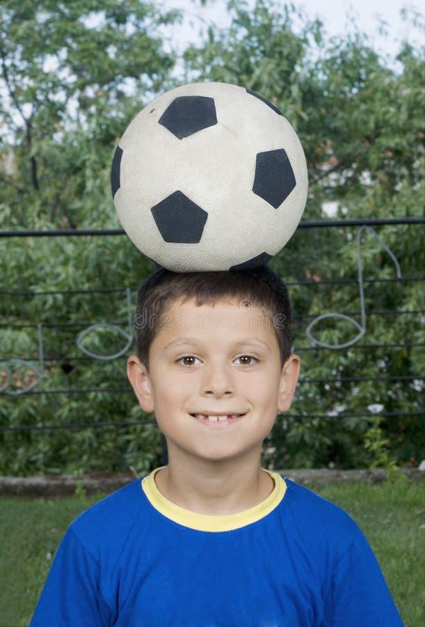 Garçon et bille de football photos stock