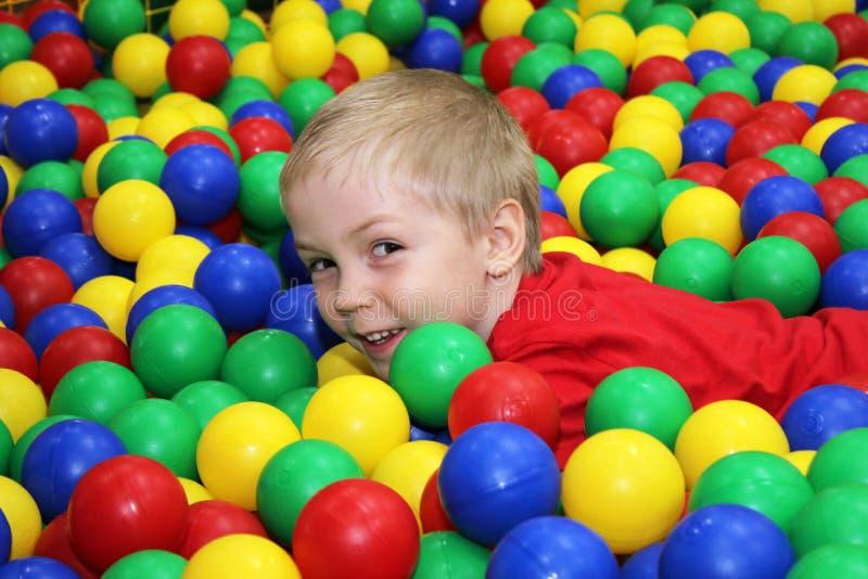 Garçon et boules en plastique colorées pour le jeu photo libre de droits