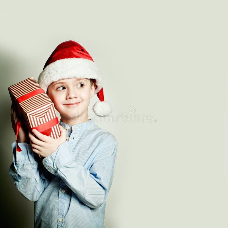Garçon et cadeau d'enfant de Noël Qu'est dans le boîte-cadeau ? photographie stock
