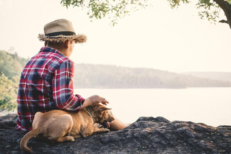 Garçon et chien asiatiques de détente de moment en nature photos libres de droits