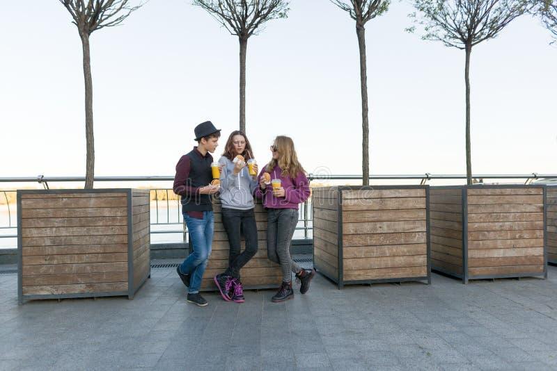 Garçon et deux filles sur la rue de ville avec les hamburgers et le jus d'orange photo libre de droits