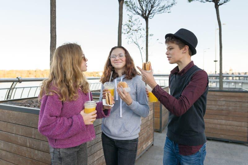 Garçon et deux filles sur la rue de ville avec les hamburgers et le jus d'orange image libre de droits