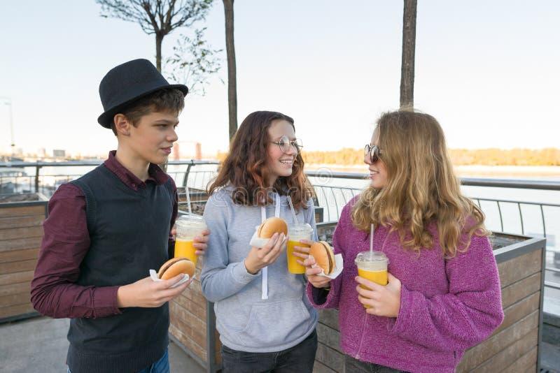 Garçon et deux filles sur la rue de ville avec les hamburgers et le jus d'orange photos stock