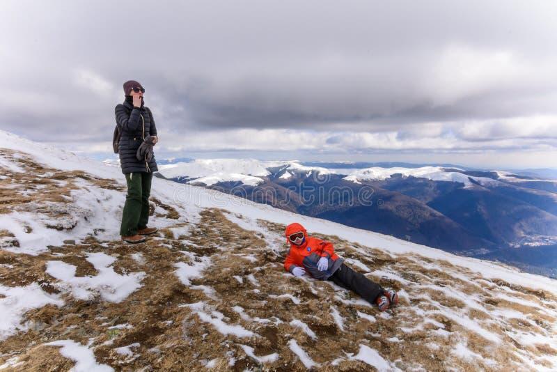 Garçon et femme au-dessus des montagnes dans l'hiver Garçon mignon de petit enfant en vêtements colorés et verres d'hiver s'étend image stock