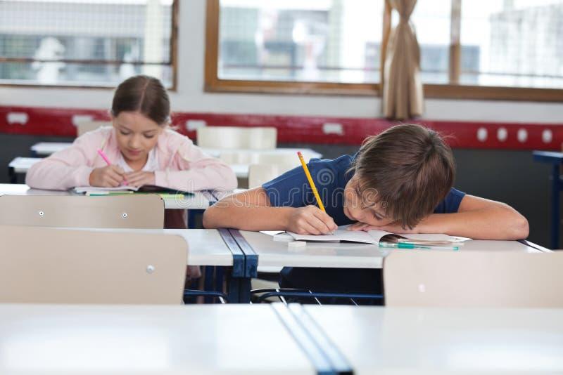 Garçon et fille étudiant dans la salle de classe photographie stock libre de droits