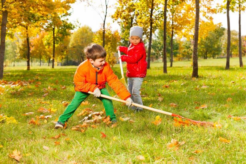 Garçon et fille avec deux râteaux fonctionnant l'herbe de nettoyage photos libres de droits