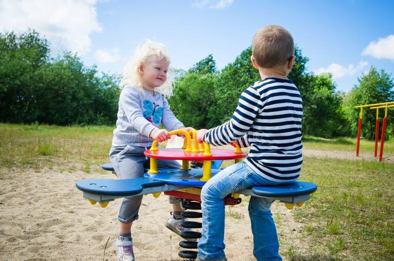 Garçon et fille balançant sur une oscillation photographie stock libre de droits