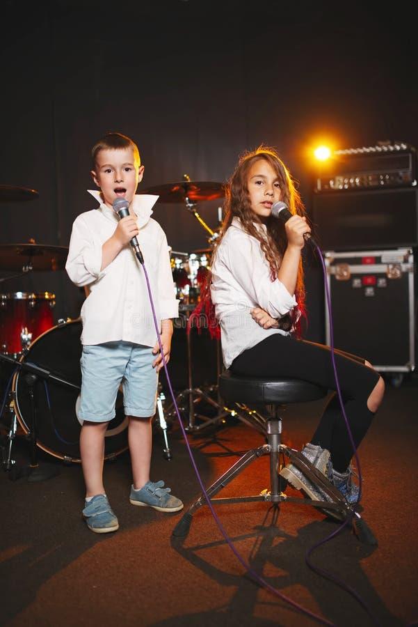 Garçon et fille chantant dans le studio d'enregistrement photos libres de droits
