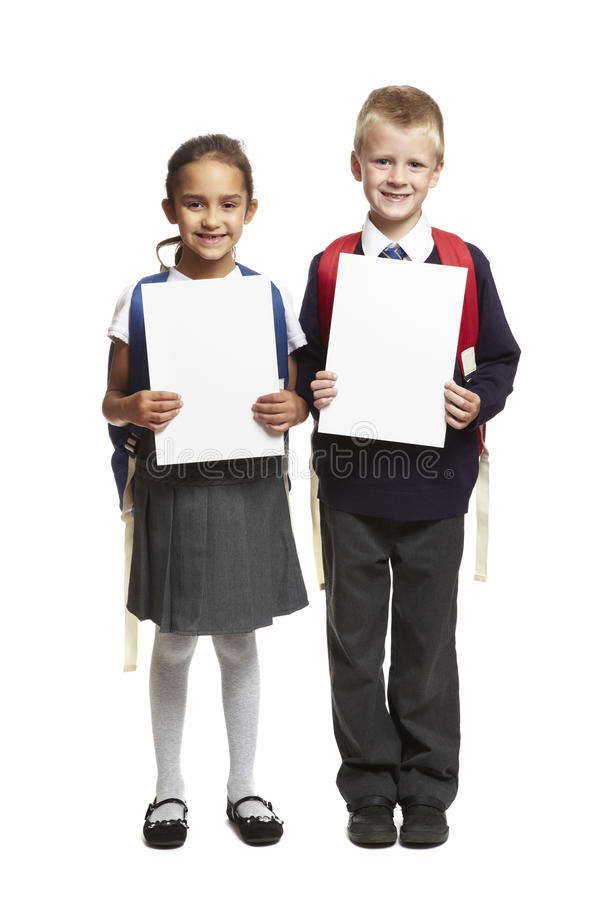Garçon et fille d'école avec les cartes blanches vierges image libre de droits