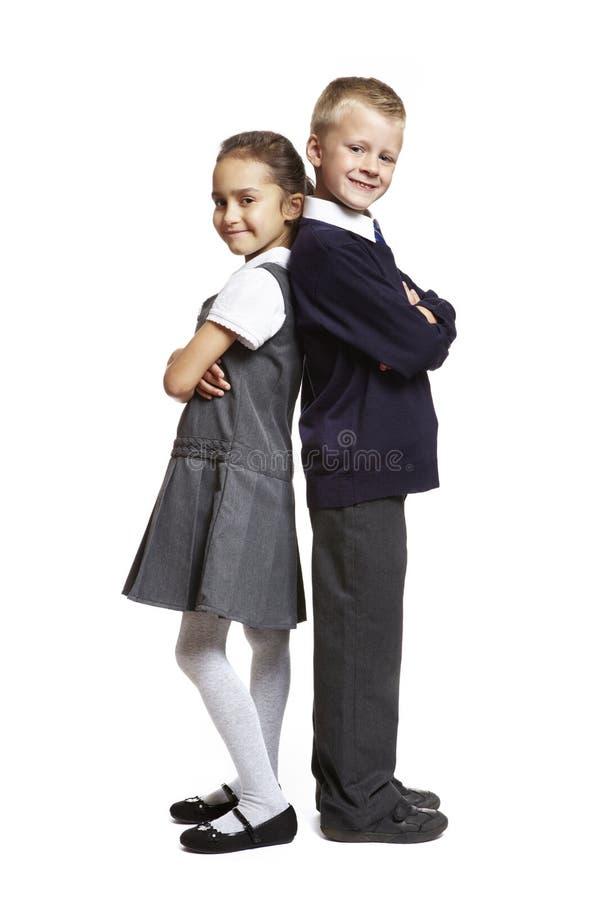Garçon et fille d'école sur le fond blanc photos stock