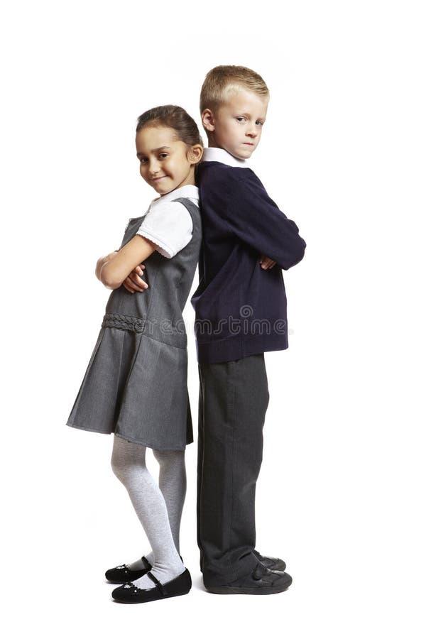 Garçon et fille d'école sur le fond blanc photos libres de droits