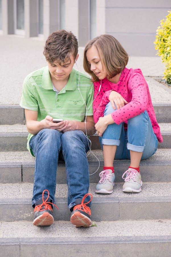 Garçon et fille de l'adolescence avec des écouteurs photographie stock libre de droits