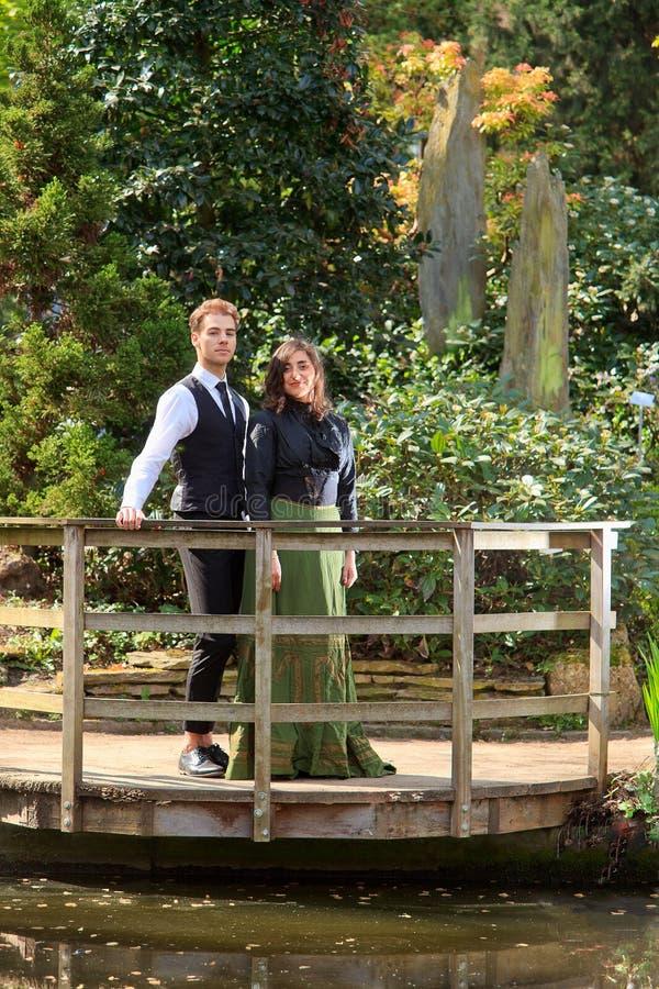 Garçon et fille de mode victorienne près de lac en parc photographie stock libre de droits