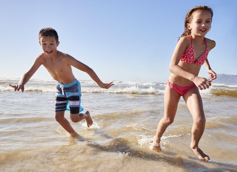 Garçon et fille des vacances d'été fonctionnant par des vagues images libres de droits