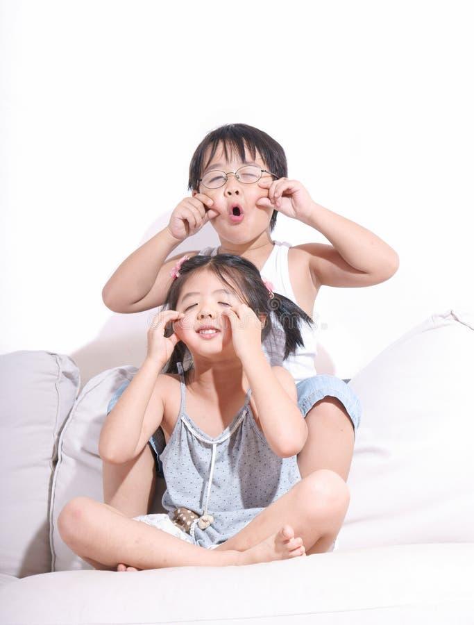 Garçon et fille effectuant des visages sur le sofa images stock