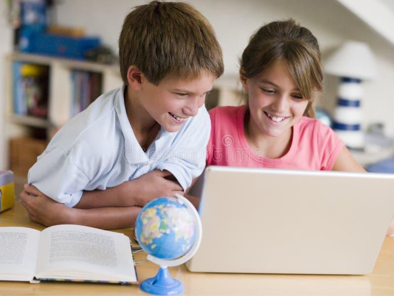 Garçon et fille faisant leur travail sur un ordinateur portatif photographie stock