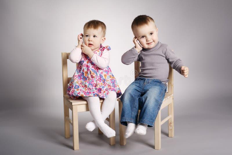 Garçon et fille jouant avec des téléphones portables images libres de droits