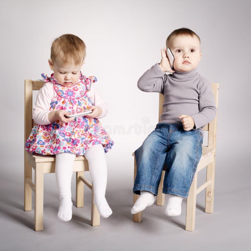 Garçon et fille jouant avec des téléphones portables photo stock