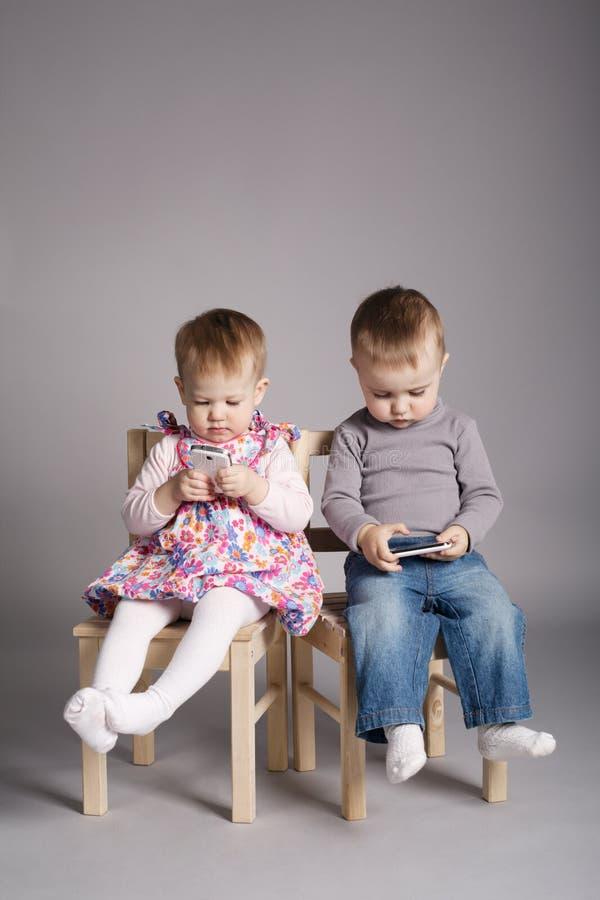 Garçon et fille jouant avec des téléphones portables photos libres de droits