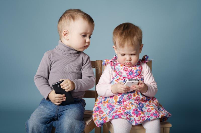 Garçon et fille jouant avec des téléphones portables image stock