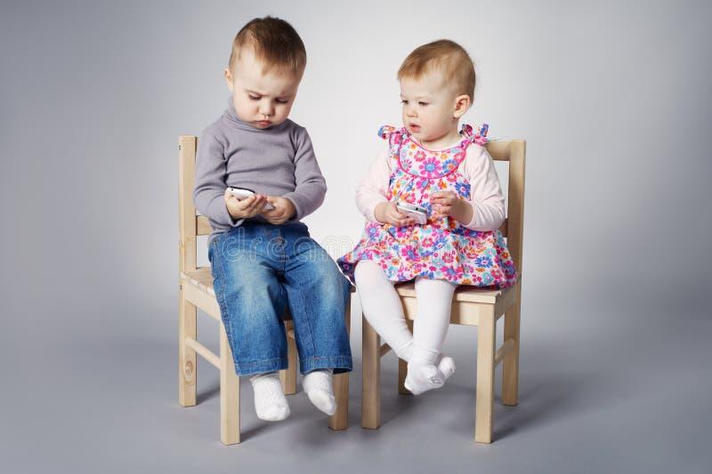 Garçon et fille jouant avec des téléphones portables photos stock