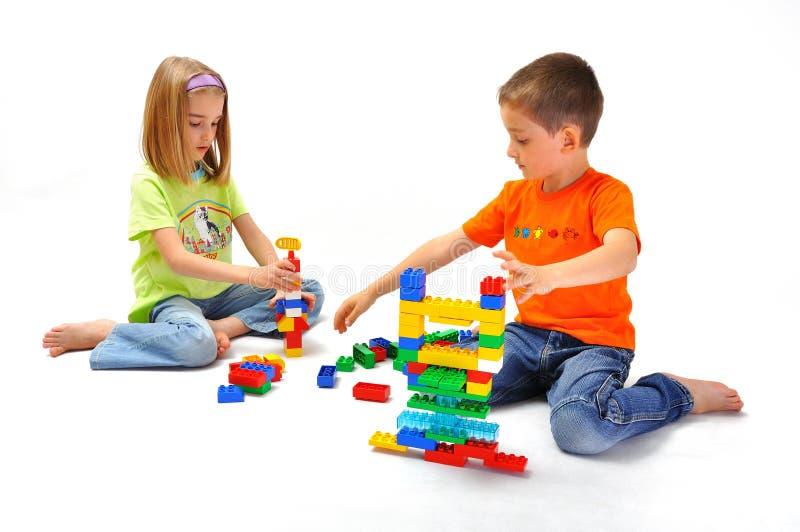 Garçon et fille jouant avec le constructeur photographie stock