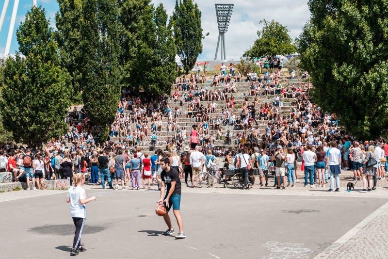 Garçon et fille jouant le basket-ball en parc à côté de la foule des personnes images libres de droits
